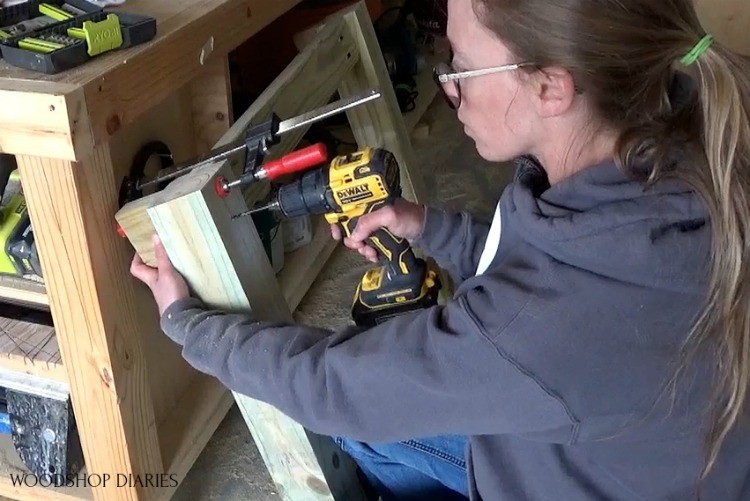 "Shara driving 4"" wood screws to attach decorative end piece to table ends"