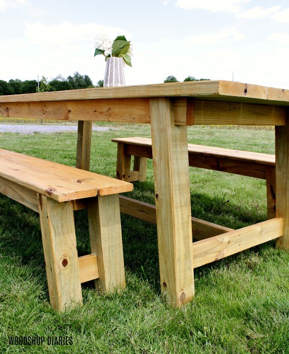 Close up of stained outdoor trestle table and bench design sitting out in front yard