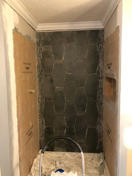 Back shower wall tile installed with small gap at top