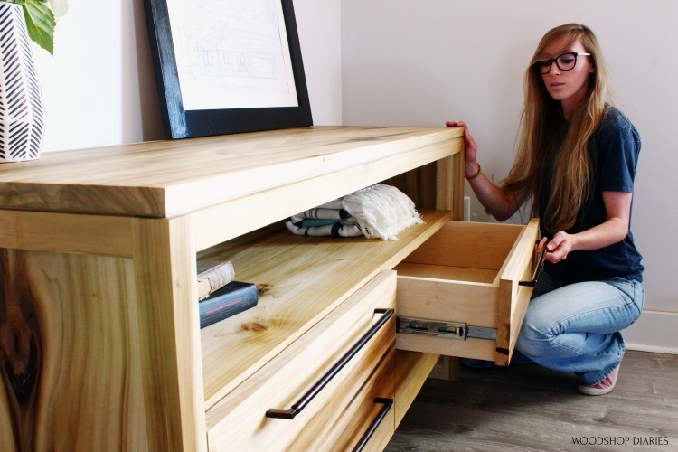 Shara Pulling drawer out of DIY modern dresser to look inside