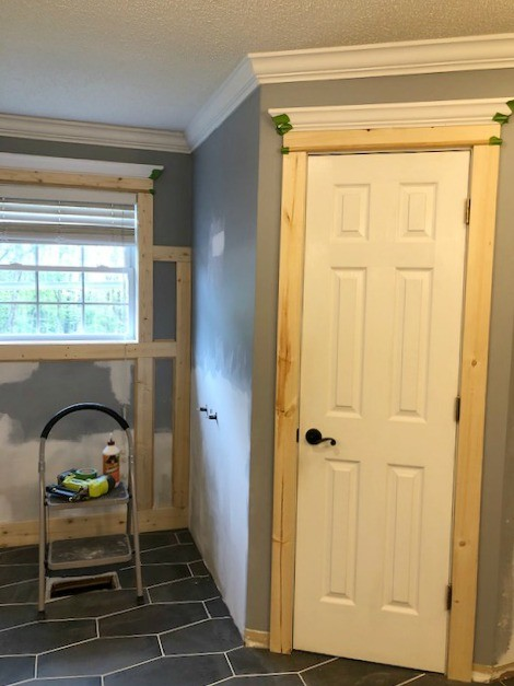 Unfinished door and window trim installed in master bathroom