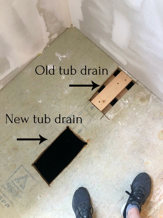 Old and new drain holes cut into master bathroom floor for tub