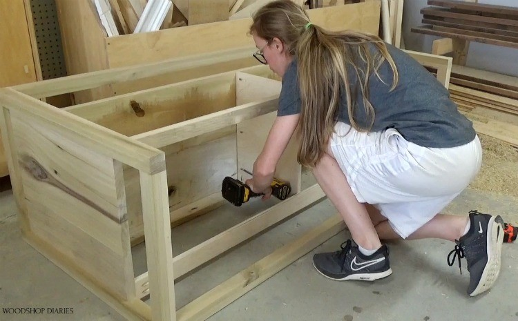 Shara screwing in drawer divider panel into dresser frame