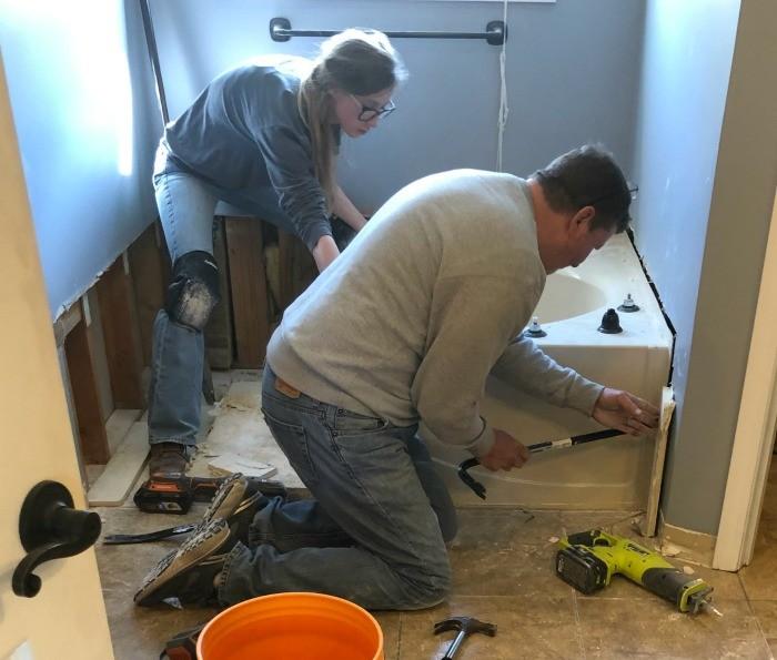 Shara and Dad tearing out bathtub in master bathroom