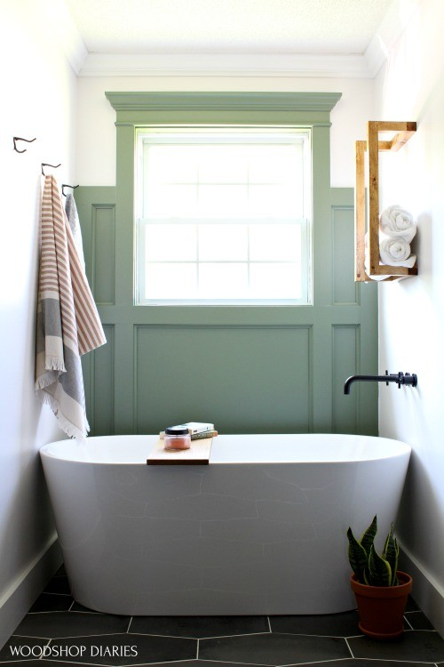 Sage Green feature wall behind free standing modern bathtub on Castlerock tile floor and white walls in master bathroom after renovation