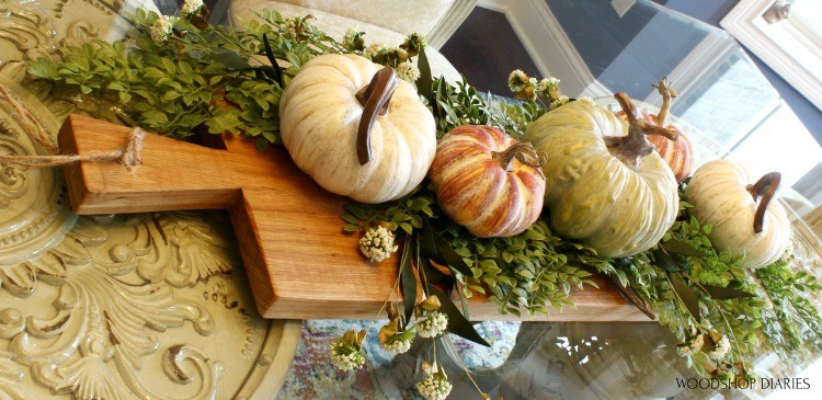 DIY Serving Board used as dining table centerpiece with pumpkins and greenery