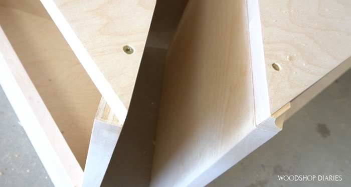 Close up of little cove trim placed on nesting table seat corners
