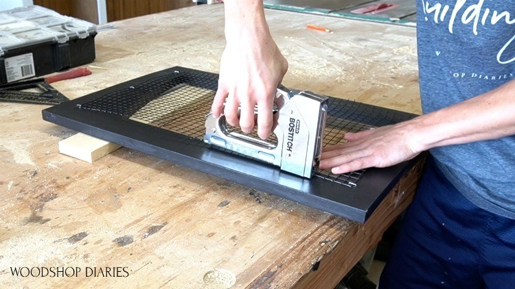 Stapling hardware mesh cloth onto back of dog crate doors