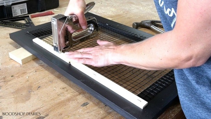 Stapling scrap wood blocks on back side of door to cover mesh edges