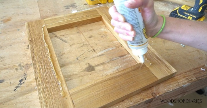 Applying clear gorilla glue to door frame for blessing box