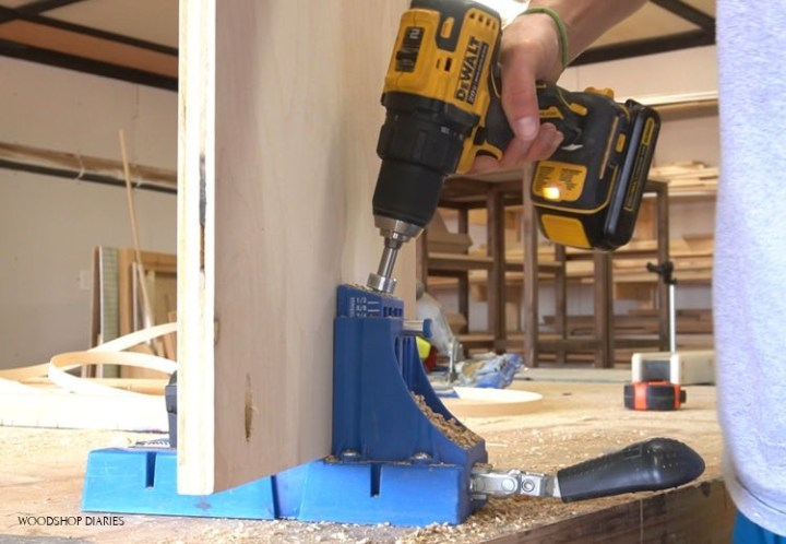 Plywood clamped in pocket hole jig with drill drilling holes
