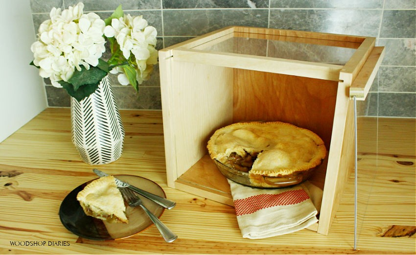 Apple pie in DIY pie carrier display box with front lid removed and a slice cut out