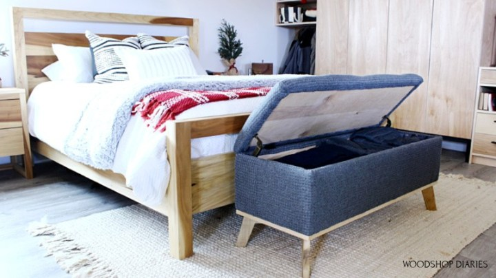 Storage bench with lid open full of blankets and clothes at end of bed