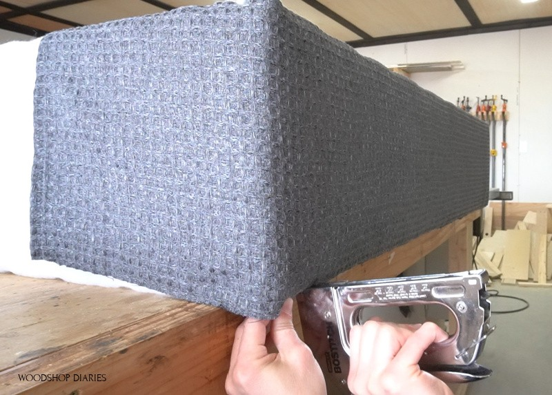 Using staple gun to secure fabric on underside of bench storage box