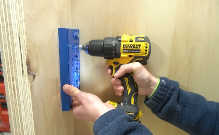Using shelf pin jig to drill holes into cabinet sides