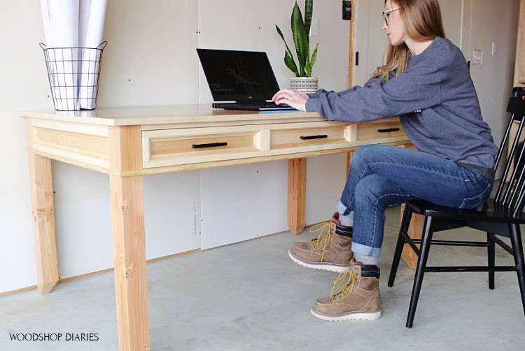 Shara Woodshop Diaries sitting at large writing desk on laptop in black chair