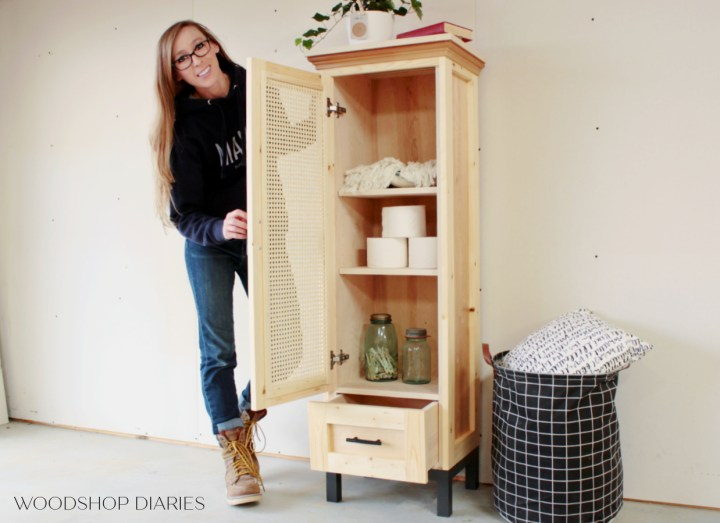 Shara holding tall linen cabinet door open to show what's inside