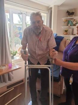 Terry, with help from Heather, stands up and stretches his legs