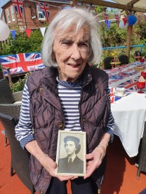 Barbara and a photo of her as a Wren (Women's Royal Naval Service)