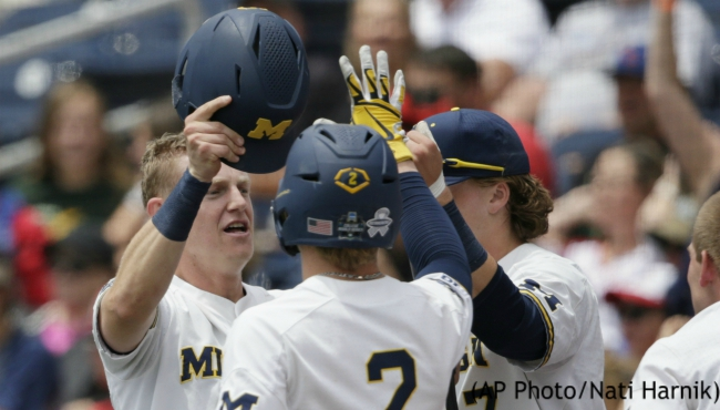 Michigan's Jimmy Kerr, left, is greeted by Jack Blomgren (2) and Jesse Franklin (7) at the dugout after scoring a run against Texas Tech on an RBI double by Blake Nelson in the first inning of an NCAA College World Series baseball game in Omaha, Neb., Friday, June 21, 2019. (AP Photo/Nati Harnik)
