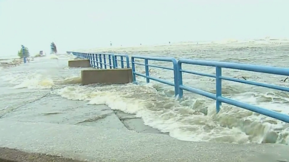 Water washes up over the pier at South Haven on June 13, 2019.
