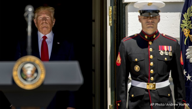President Donald Trump emerges from doorway to South Lawn of White House