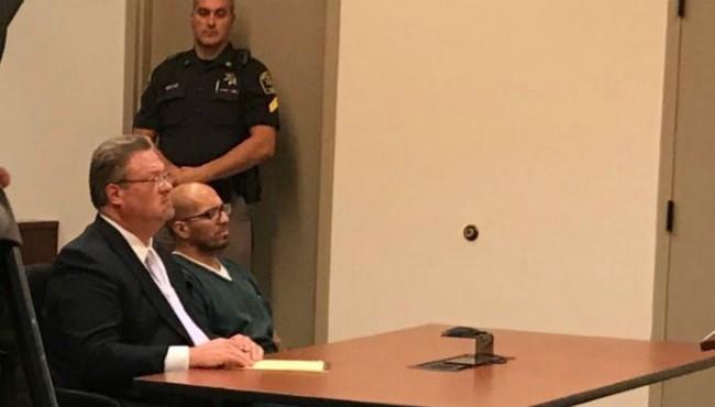Frederico Cruz sits behind desk with defense attorney