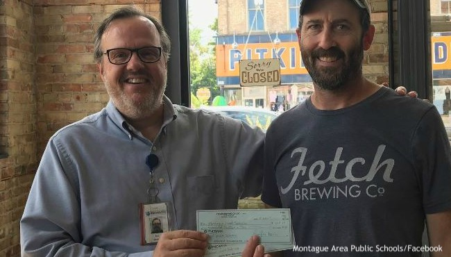Brewery worker hands over check to school district official