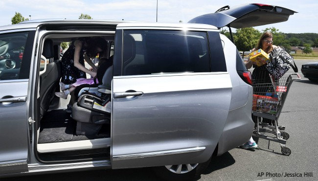 Woman loads groceries into back of minivan sliding doors open revealing girl strapping in younger girl to seat