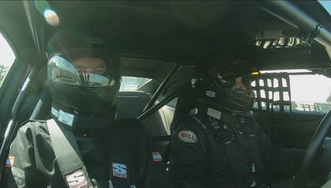 Rick Albin suited up in passenger seat of race car