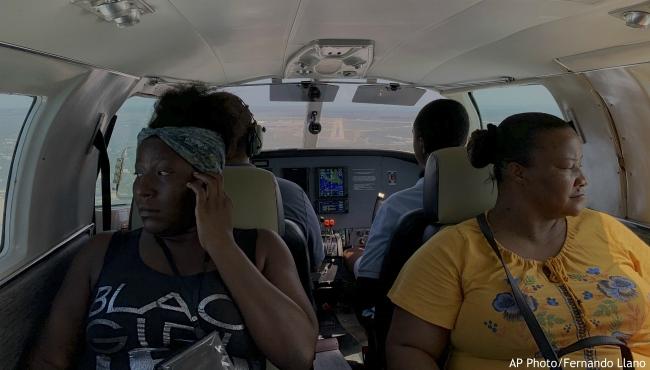 "Dimple Lightbourne, left, and her mother Carla Ferguson sit in a plane as it approaches to land in Nassau after they were evacuated from Abaco Island, in the Bahamas, Monday, Sept. 9, 2019. ""We don't know where we're going to stay,"" said Ferguson, a 51-year-old resident of Treasure Cay. (AP Photo/Fernando Llano)"