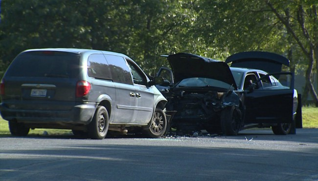 minivan and wrecked car rest on side of road