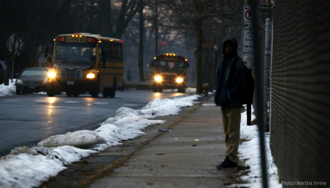 In this Feb. 5, 2019, photo, a student waits for a bus outside the abandoned John C. Clark Elementary and Middle School in Hartford, Conn. (AP Photo/Martha Irvine)