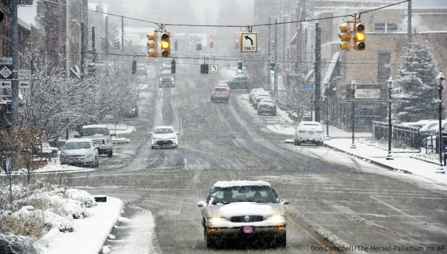 Traffic creeps through downtown Niles, Mich., Monday, Nov. 11, 2019, after a fall storm dumped several inches of snow in southwest Michigan. (Don Campbell/The Herald-Palladium via AP)