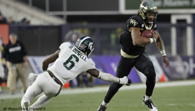 Wake Forest's Jamie Newman, right, runs past Michigan State's David Dowell (6) during the first half of the Pinstripe Bowl NCAA college football game Friday, Dec. 27, 2019, in New York. (AP Photo/Frank Franklin II)