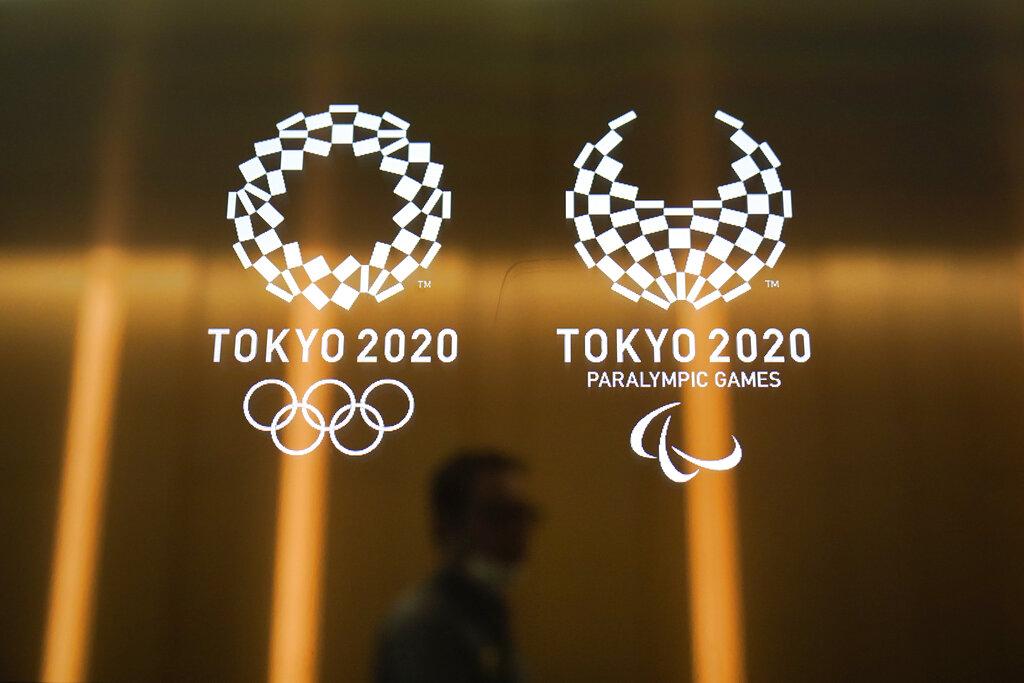 In this June 11, 2019, file photo, a man walks past the Tokyo 2020 Olympic logos in Tokyo.(AP Photo/Jae C. Hong, File)