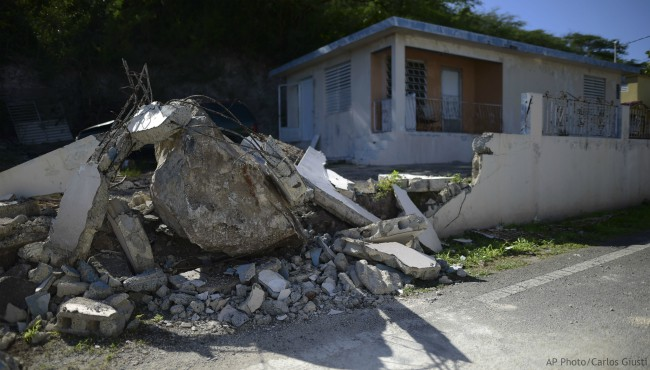 A big rock sits amid the rubble of the low wall it destroyed when it rolled down from a nearby cliff during a magnitude 5.9 earthquake in Guanica, Puerto Rico, Saturday, Jan. 11, 2020. (AP Photo/Carlos Giusti)