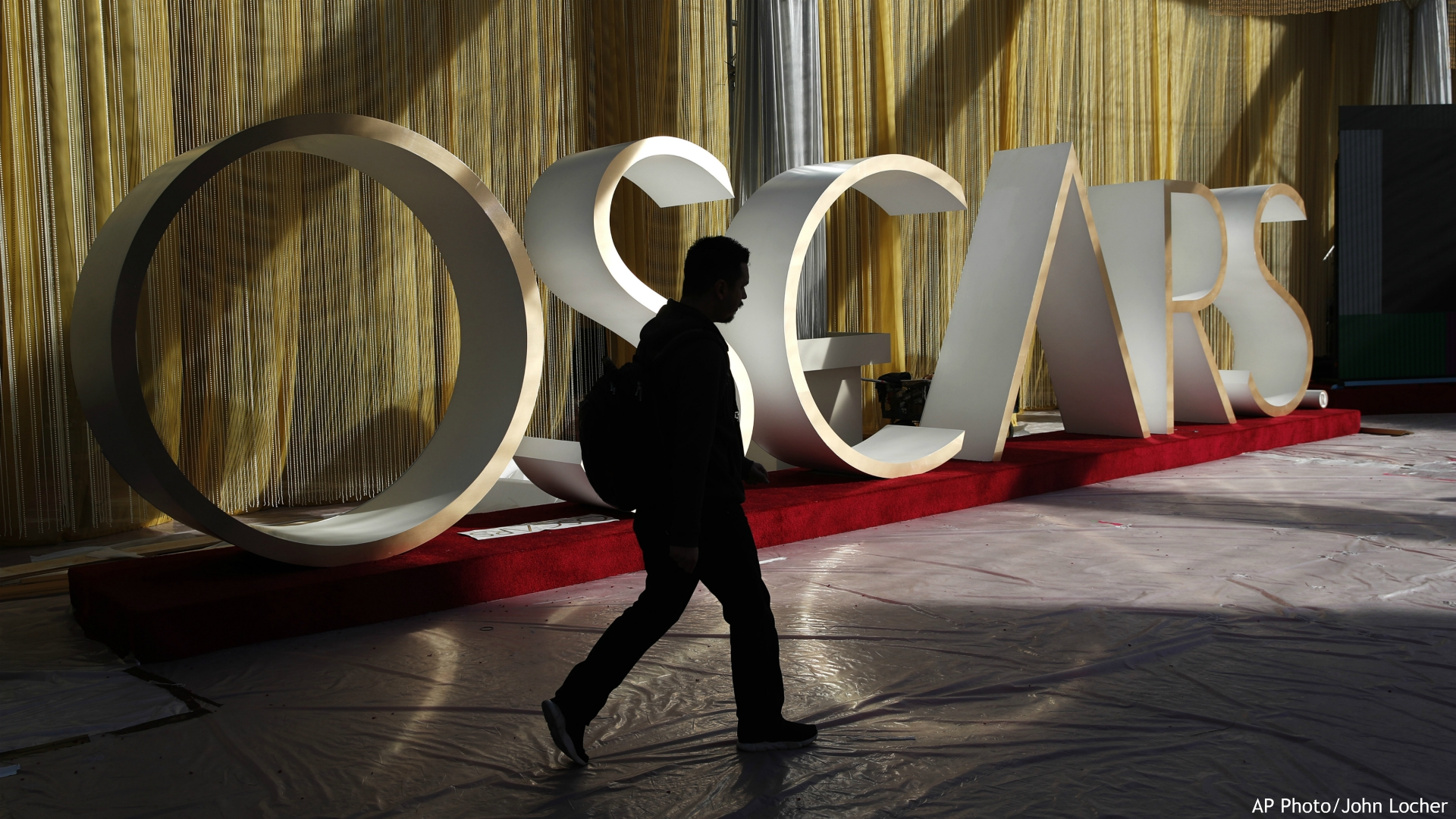 A worker walks along the red carpet during preparations for Sunday's red carpet arrivals at the 92nd Academy Awards at the Dolby Theatre, Friday, Feb. 7, 2020, in Los Angeles. (AP Photo/John Locher)