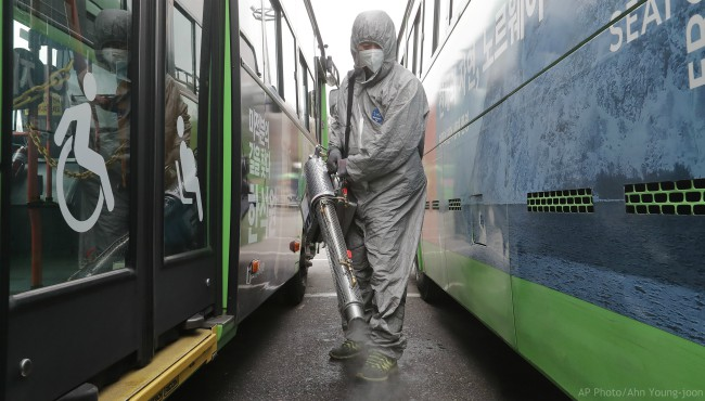 A worker wearing a protective suit sprays disinfectant as a precaution against the coronavirus at a bus garage in Seoul, South Korea, Wednesday, Feb. 26, 2020.