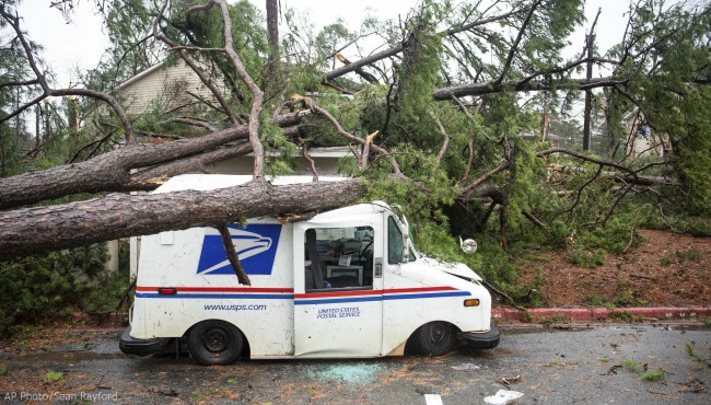 Fallen trees rest on a damaged postal truck at an apartment complex where a reported tornado passed through Thursday, Feb. 6, 2020, in Spartanburg, S.C. (AP Photo/Sean Rayford)