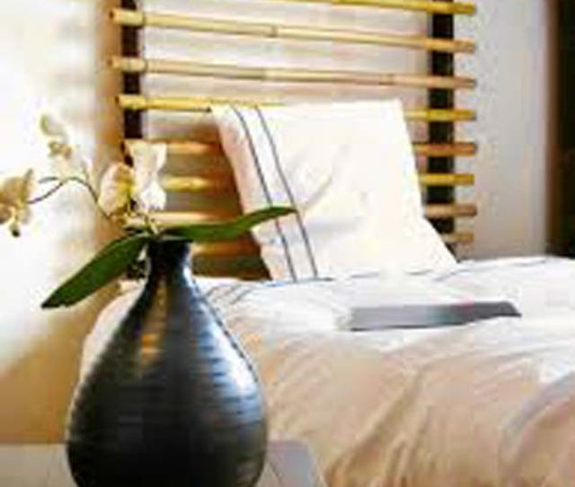 Headboard Made From Two Wooden Sticks And Some Bamboo Poles