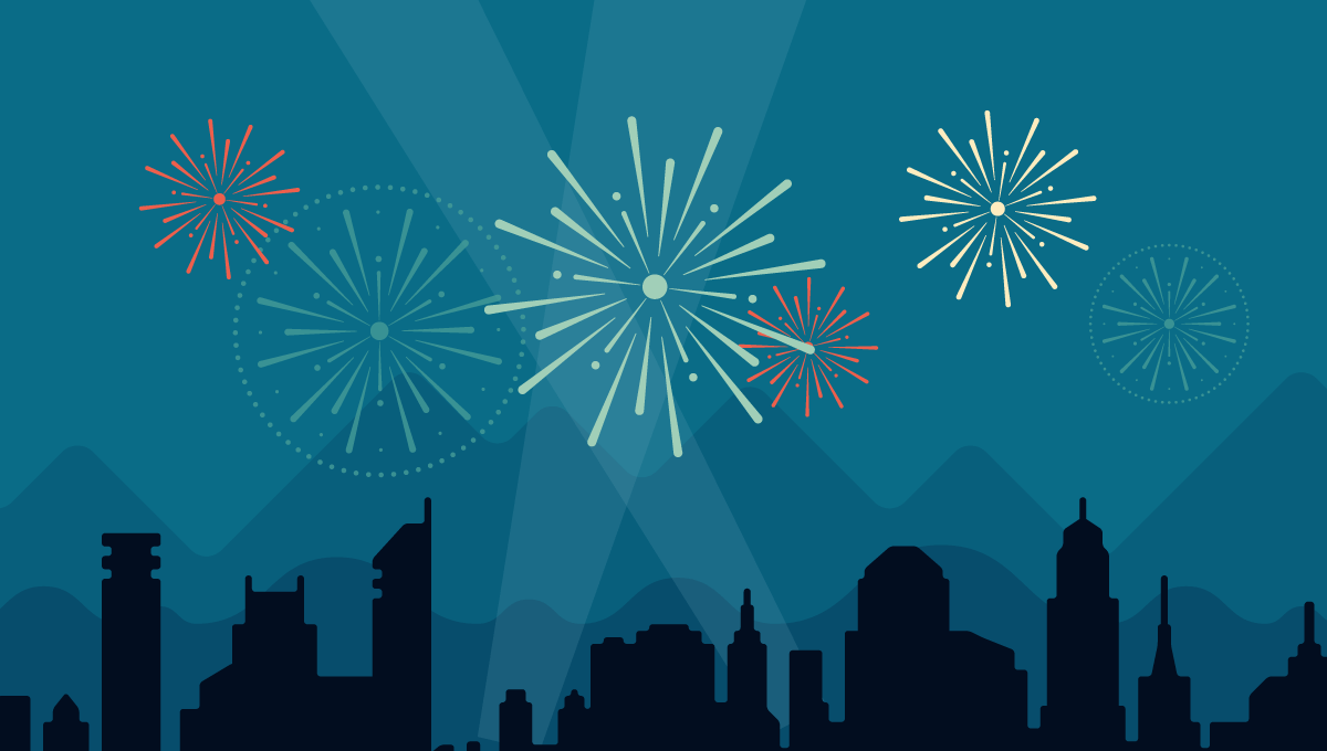 Dark blue sky with darker blue, generic city skyline. Light blue search lights and fireworks light up the sky.