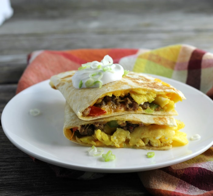 Breakfast quesadillas stuffed full of eggs, sausage, tomatoes, green peppers, onion, and cheddar cheese.