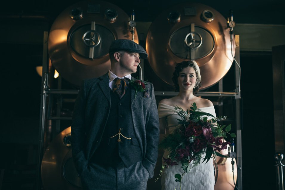 Bride and groom standing infant of copper brewing tanks