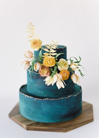 Teal coloured wedding cake with yellow floral decor