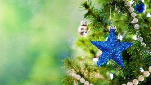 Glittering blue Christmas star on Christmas tree