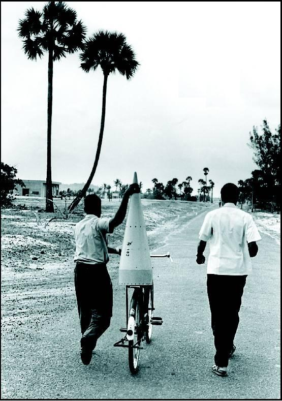 16. An ISRO scientist transporting the nose cone of a rocket on a cycle - Thumba, Kerala, 1968.