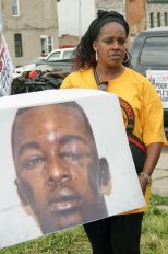 Suzette Cook Robinson holds picture of her son, Joshua Robinson, brutalized by Providence, R.I. police.