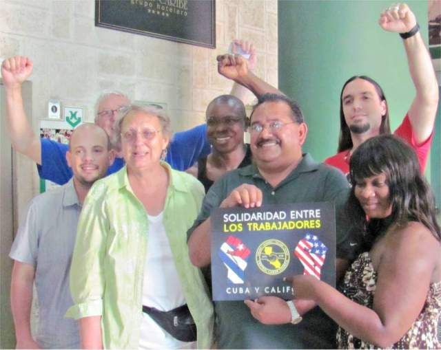 """A few members of the U.S. union delegation to 2016 May Day celebration in Cuba with """"Worker Solidarity - Cuba and California"""" sign."""