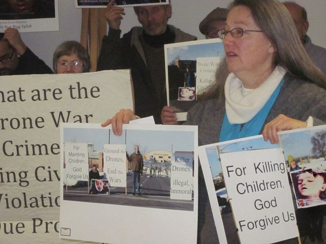 Mary Ann Grady Flores holds photos she was arrested for taking at Hancock AFB anti-drone protest.WW photo: Minnie Bruce Pratt